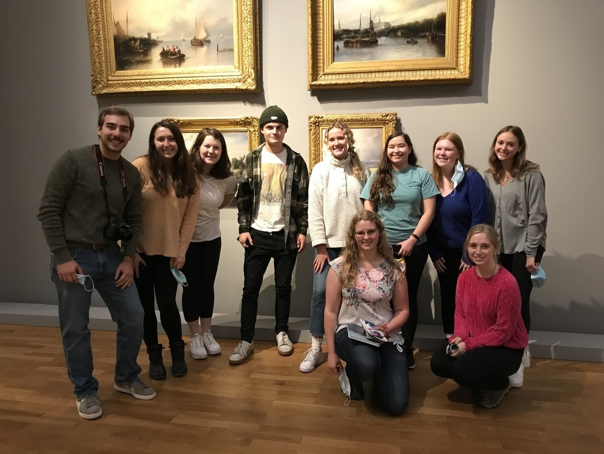 10 students in a museum with paintings behind
