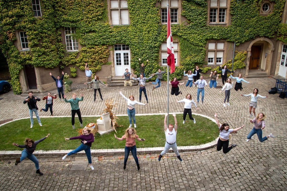 Students in the courtyard of the château jumping