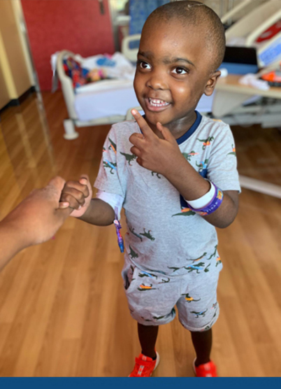 Image. Dontrell stands in his hospital room holding his mom's hand.