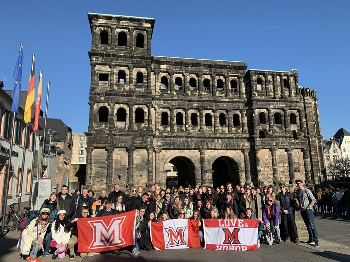 MUDEC 2020 Spring class with 3 Miami flags in front of the Porta Nigra