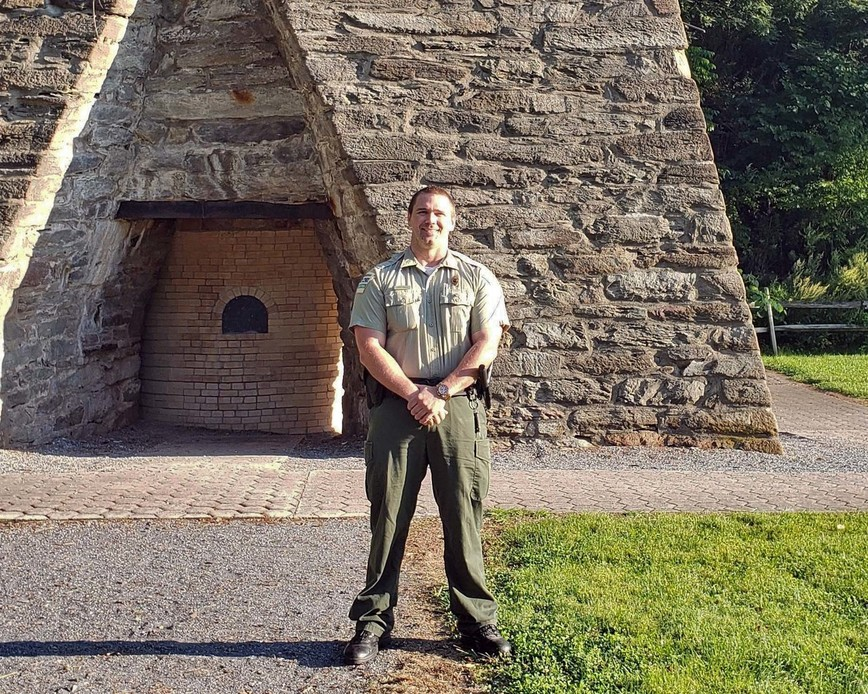 Christopher Houck stands in front of a stone structure wearing a DCNR uniform.