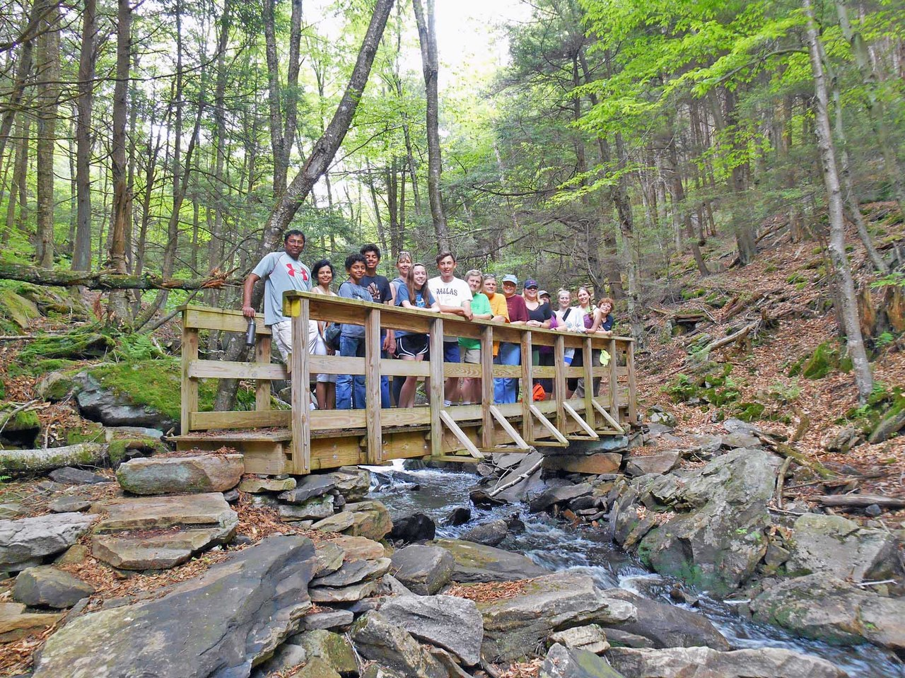 A large group of people stand on a trail bridge over a rocky mountain creek.