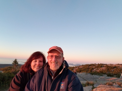 Connie Johnson and her husband standing outside under a blue sky, wearing jackets