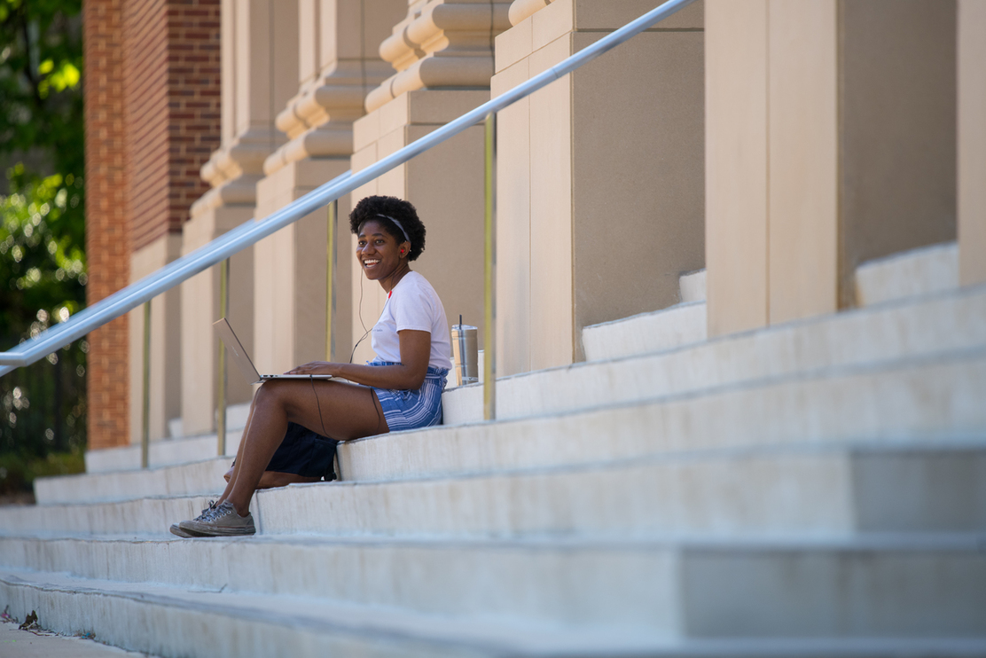 Student sitting on the Student Union steps on a laptop smiling