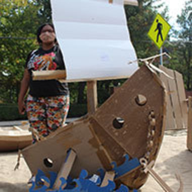 Student poses with pirate ship made of cardboard