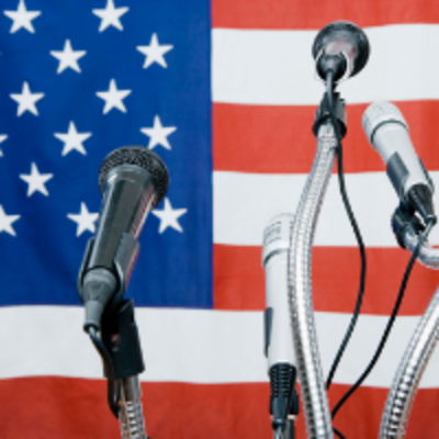 microphones in fromt of a US flag