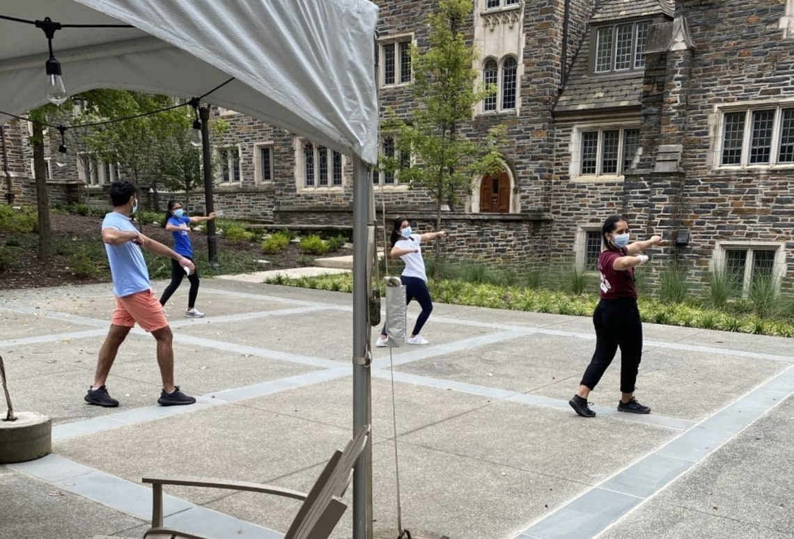 Four students practicing proper physical distancing and wearing masks while practicing a dance routine