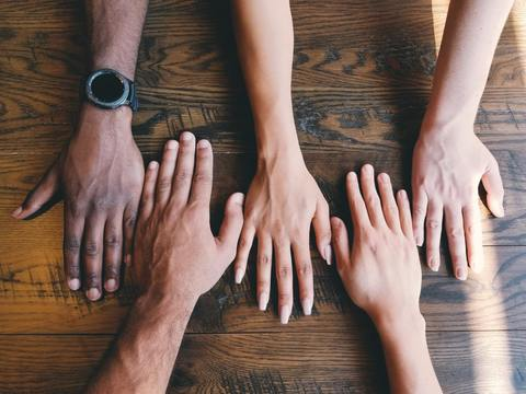 Hands of various skin tones lined up palm down on a wooden table.