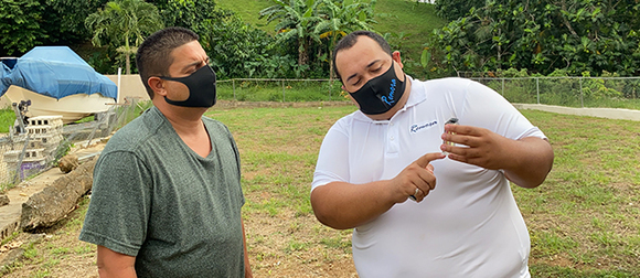 Omar Negron-Ocasio (right) showing water sample to colleague