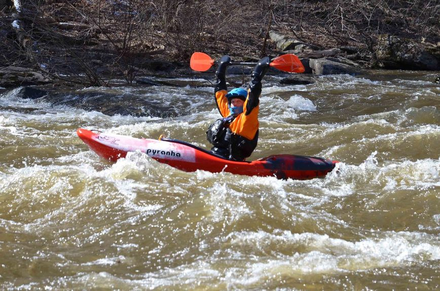 A person rides a kayak in a fast creek wearing a life vest, helmet, and gloves.
