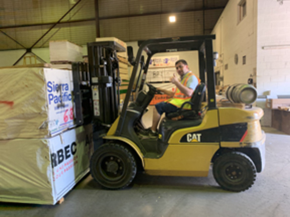 Christopher driving a yellow forklift about to lift some lumber.