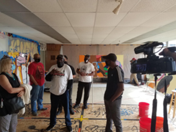 People Inc. Vice President Jocelyn Bos (far left) visited the artists commissioned to do the murals for the People Inc. Jefferson Avenue Apartments.