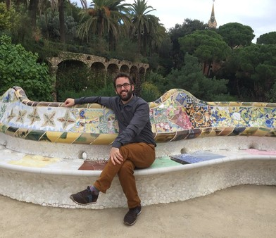 Kevin sits on a colorful serpentine bench in Barcelona