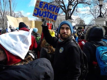 Kevin holds up a sign 'earth justice' as part of a march outside gates