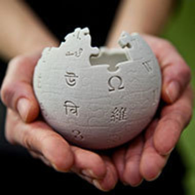 Hands holding Wikipedia puzzle ball