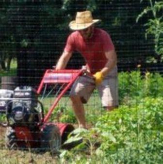 Kevin operates a tiller in a garden