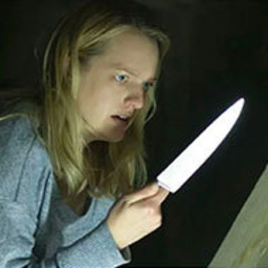 Scene from movie with female character holding knife