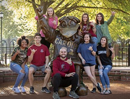 Group of students around mascot statue