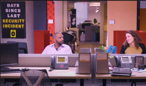 Screen shot of a funny video about cybersecurity. Two people sit at desks in an office. A sign above one of their shoulders says 'Days since last security incident - 0'