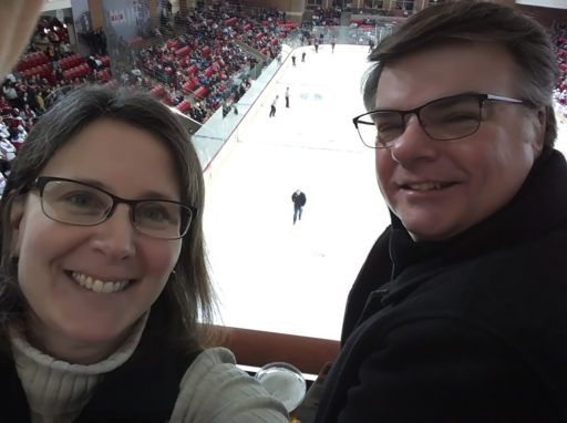Dennis Schwind (right) and his wife Kristen (left) at a hockey game