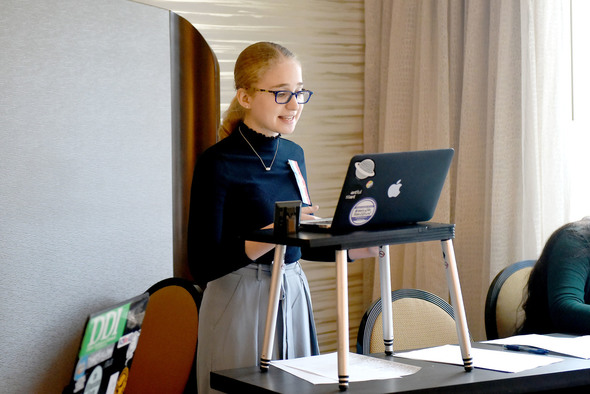 Student delivers speech, reading from laptop