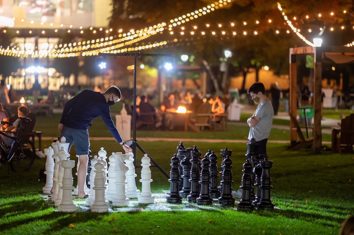 Photo of students playing chess with giant pieces on Library Lawn