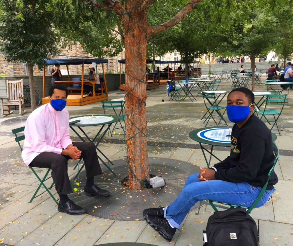 Brother Joshua of the Center for Muslim Life talking to a student on the Bryan Center Plaza. Both are wearing masks and physically distanced.