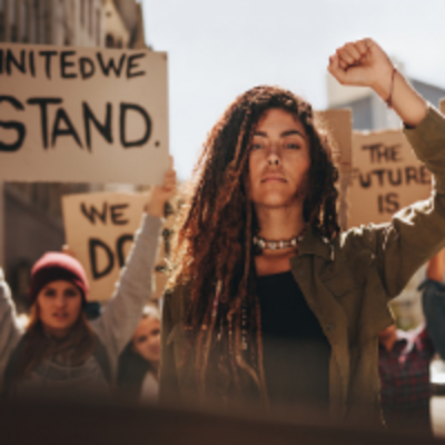 Photo of a woman at a peaceful protest with her fist in the air. Behind her, a sign reads