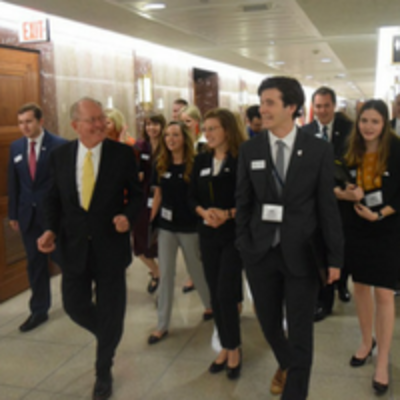 Students walking with Senator Lamar Alexander