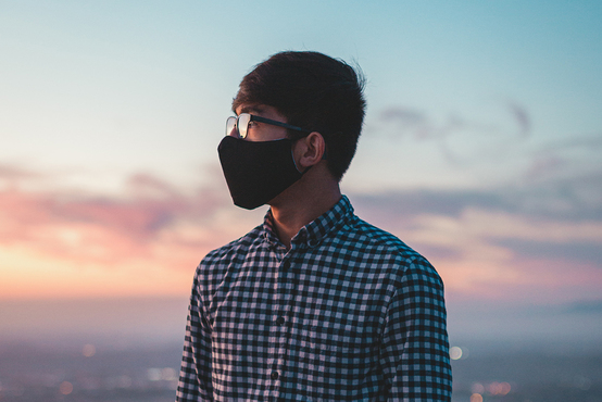 Masked male student watching the sunset