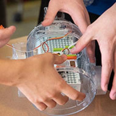 Students' hands working on robotic part