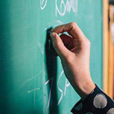 Closeup of hand writing on chalkboard