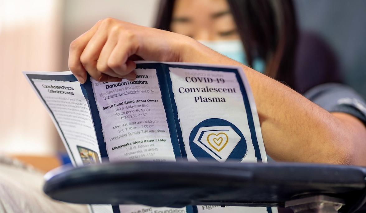 A student donating plasma reads a COVID-19 Convalescent Plasma brochure