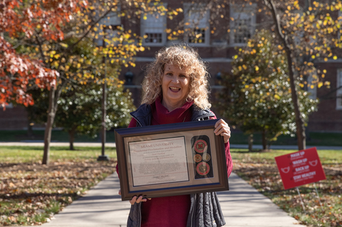 Tarah Trueblood stands near the campus seal and holds her DEI taskforce award up