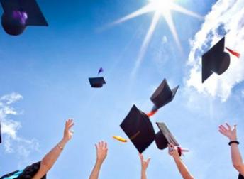 Hands throwing graduation caps into sunny blue sky