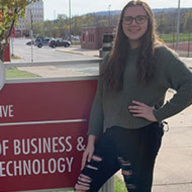 Alexis Boyle next to Eberly College of Business and Information Technology sign