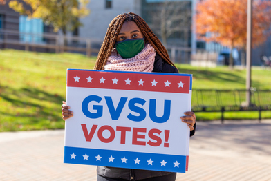 student holding GVSU Votes! sign