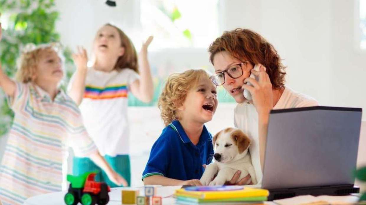 Photo of mother working at home with children