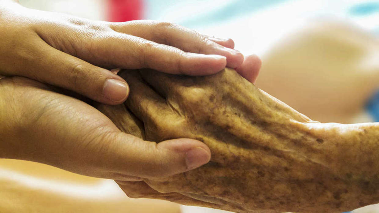 Photo of young person holding elderly person's hand.