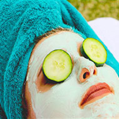 closeup of woman with mud mask and with cucumber slices over eyes and hair in towel