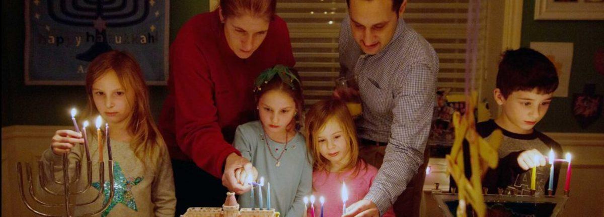 family lighting hanukkah candles