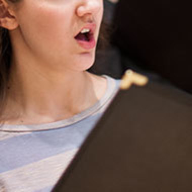 student sings with music folder in front