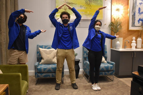 3 members of the first-year advisory council wearing masks in duke blue jackets spelling out F-A-C with their arms