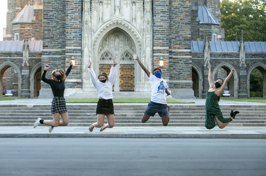 Photo of 4 students in mid-jump in front of the Duke chapel