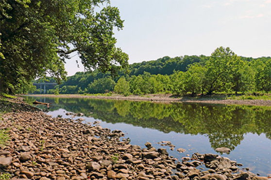 A river flows past rocky shores filled with trees.