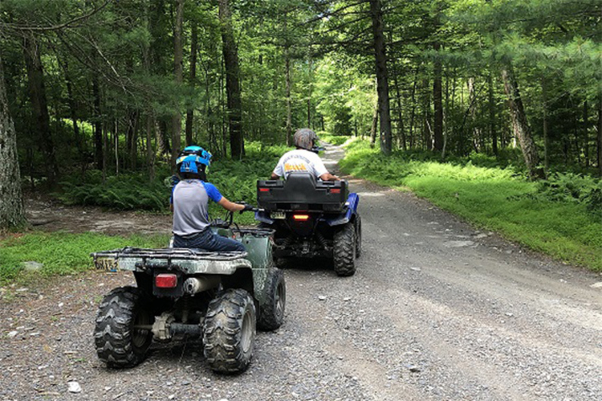 Two people sit and ride two all terrain vehicles on a gravel road in a forest.