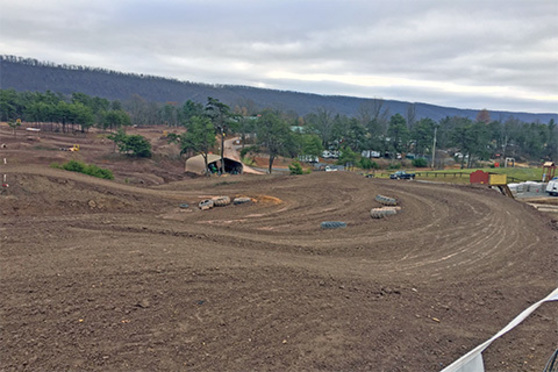A wide, dirt track curves and twists in a driving course, with trees and small buildings.