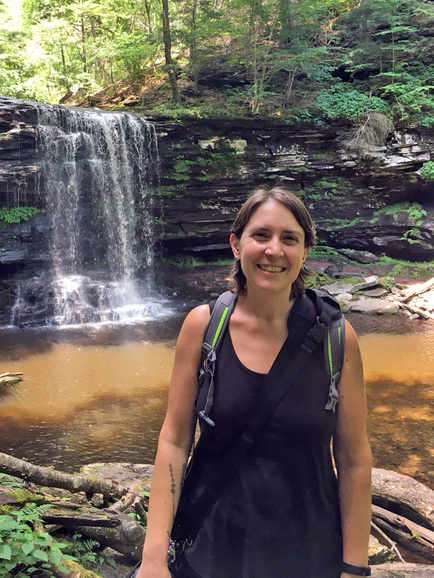 A woman wears a packback while standing in front of a waterfall and pool.