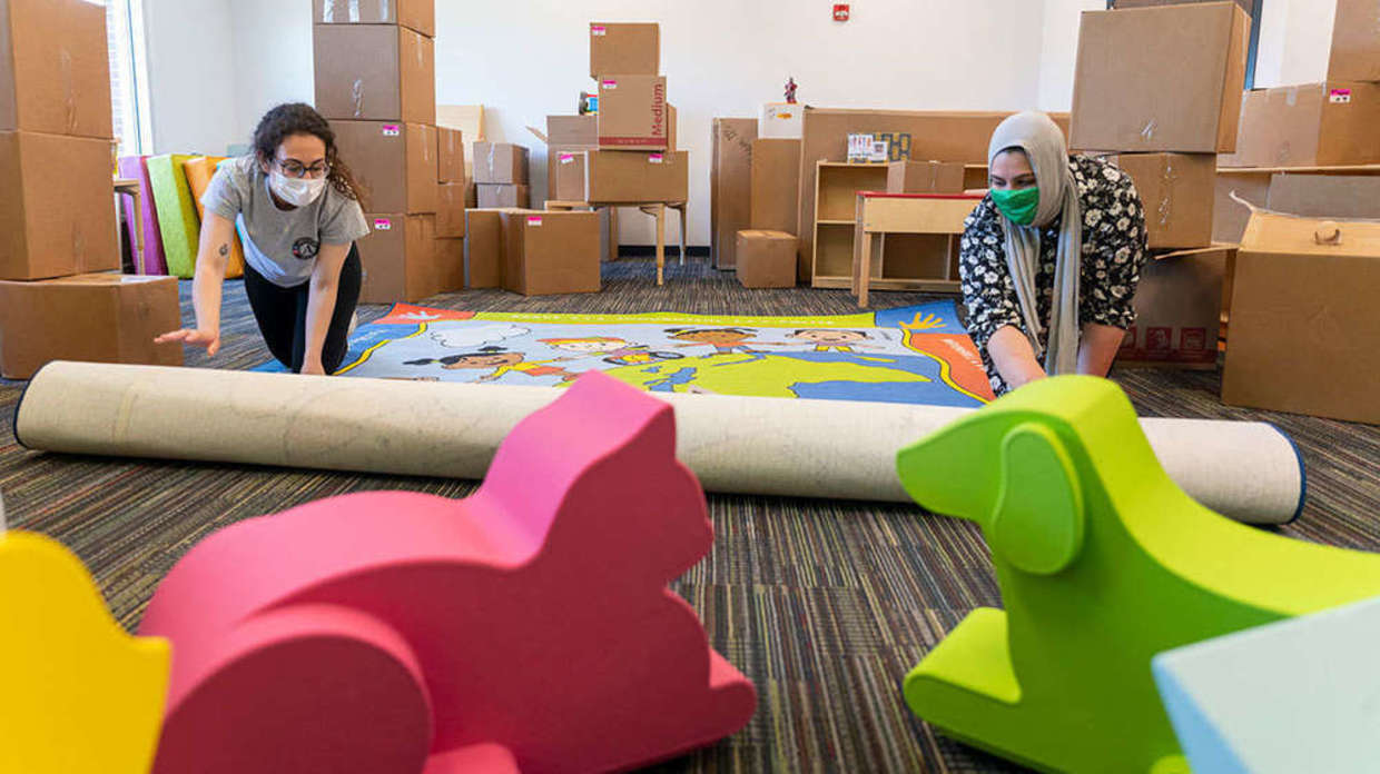 Photo of Celine Marcos and Samantha Musleh roll out a rug at the new Robinson Community Learning Center (RCLC) in South Bend.
