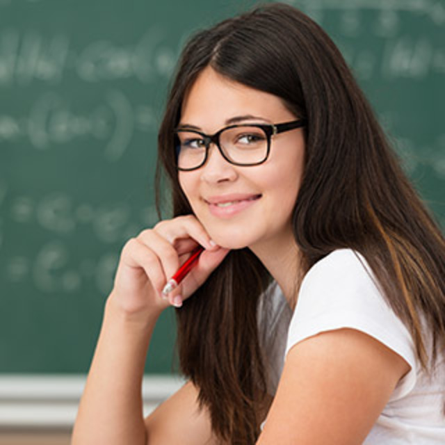Girl holding a pen next to her face with a chalk board behind her.